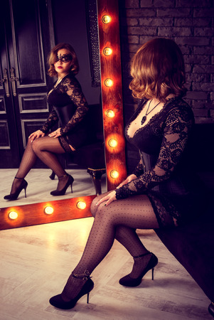 Sensual beautiful woman in lace mask looks in the mirror. Beautiful woman in the mirror. Retro glamor vintage woman Kho ảnh