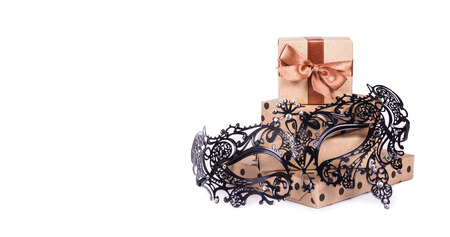 Beautiful lace mask. Beautiful metal carnival mask. Fancy mask. Gifts and decorations. Stack of gift boxes on white background. Copy space Stock Photo