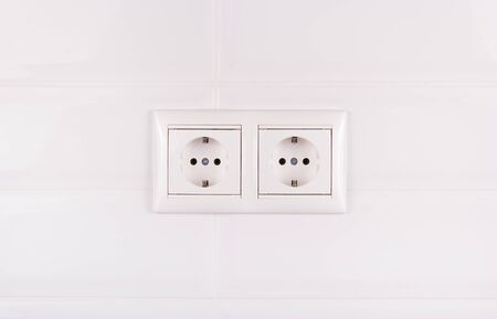 Double socket on white tile background. European electrical outlet
