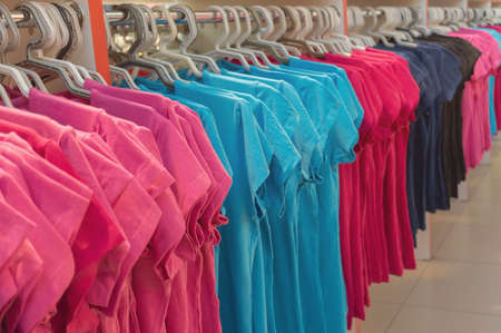 Row of colorful T shirts on hangers. Fashion retail shop display. Clothing business concept. Stock fotó