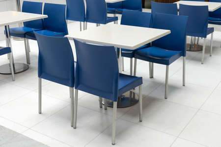 Interior of public dining area with blue plastic chairs and white tables. Empty table on food court in business shopping center, modern interior design.