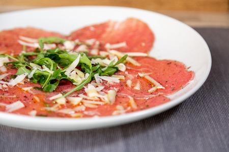 Primo piano di carne di carpaccio con parmigiano e rucola in un piatto bianco su un tavolo di legno. Con olio d'oliva. Archivio Fotografico