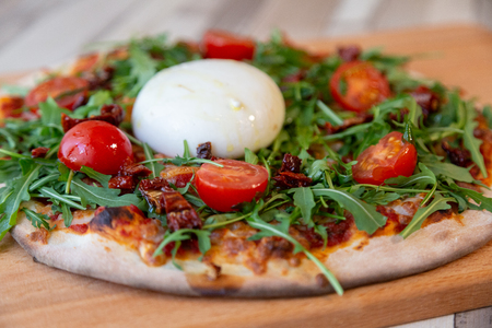 Side view of a pizza on a wooden board with cherry tomatoes, arugula, and burrata cheese on a wooden table and brick wall for background Zdjęcie Seryjne