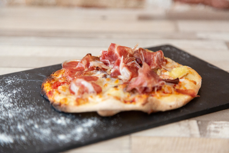 Close up of ham pizza on a blackboard on a wooden table with flour ready to eat
