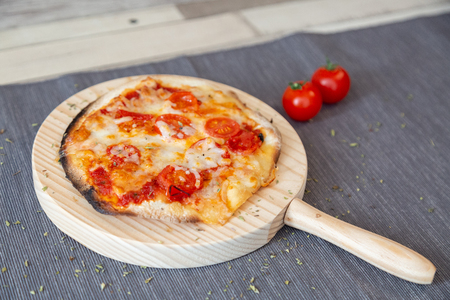 A small margarita pizza with cherry tomatoes and cheese in a circle wooden board in a gray tablecloth and wood, garnish with cherry tomatoes 免版税图像