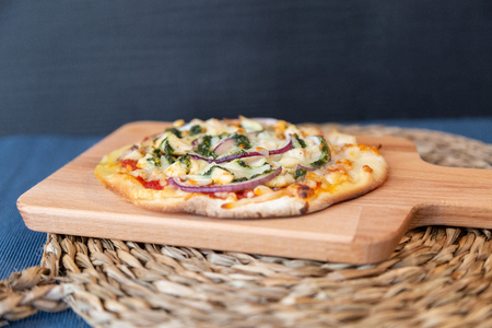 Side view of a pesto pizza with purple onion on a wooden board on raffia circle with a blue tablecloth ready to eat
