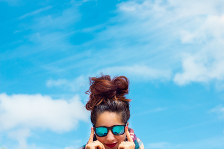 brunette girl with blue glasses and a big messy bun, red lips and nails with the sky as background