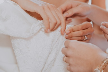 Bride getting ready to get married. Brides hands with ring unbuttoning white wedding dress with other helping hands