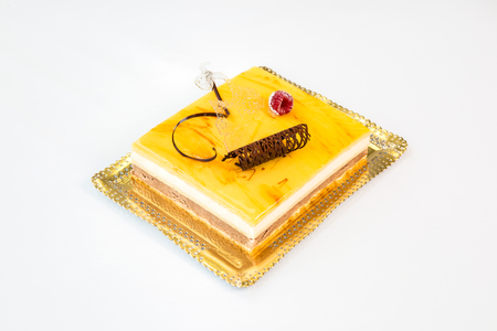 beautiful yellow cake on a gold tray on white background