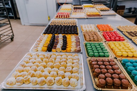 many different sweet dishes prepared on the metal table of a food factory