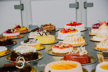 many different cakes prepared on the metal table of a food factory Foto de archivo