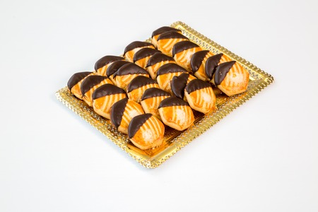 chocolate cookies on a gold tray with white background