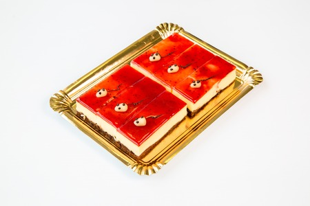 beautiful cheesecake on portions on a gold tray on white background