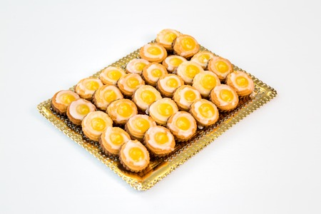 yellow cherry cookies on a gold tray with white background