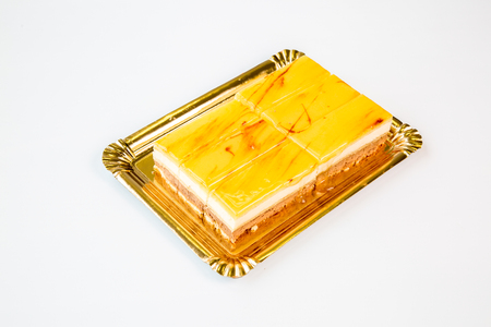 beautiful yellow egg cake on a gold tray on white background