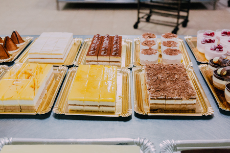 many different sweets prepared on the metal table of a food factory Foto de archivo