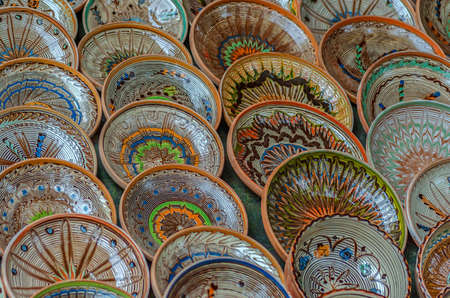 Background with Romanian traditional ceramic in the plates form, painted with specific patterns from Horezu area.