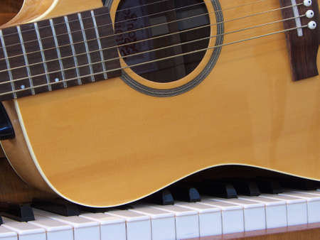 Acoustic Guitar on piano keyboard Stock Photo