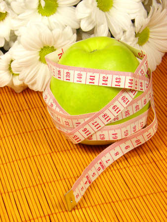Green apple, flowers and measuring tape  Stock Photo