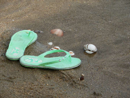 Slippers, shells on the beach Stock Photo