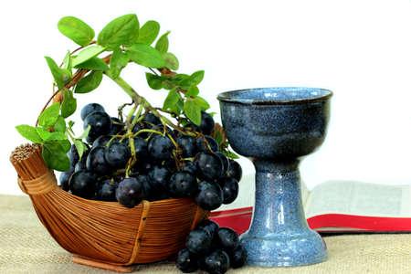 santa cena: Uvas, cáliz y Biblia abierta Foto de archivo