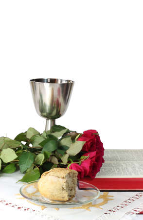 Silver chalice, roses, bread and Bible