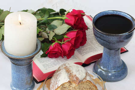 Candle, chalice, bible, roses and bread Stock Photo