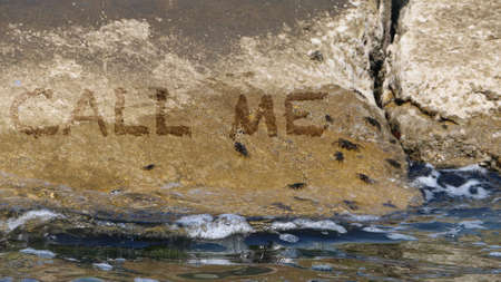 call me: Call me written on the rocks by the sea