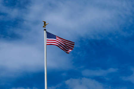American flag on pole waving in the wind against blue sky background Stockfoto