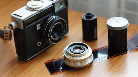 Accessories from old film cameras. A still life of accessories from old film camera: camera, lens, film cassette, piece of film, film container