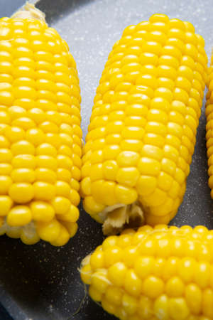 Fresh cooked yellow corn cobs lie on a gray dish
