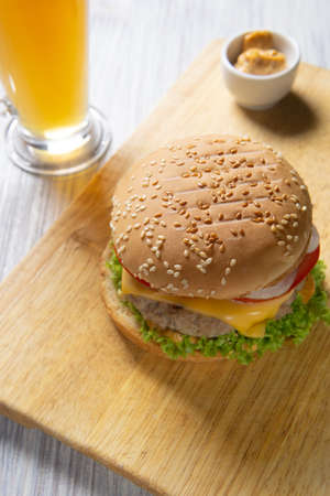Burger with beef patty, salad, a slice of tomato and cheese, onions and sauce with paprika in a grilled bun with sesame Zdjęcie Seryjne
