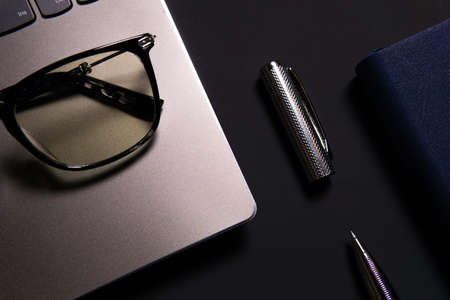 Notebook, laptop, glasses and pen on the table. Concept of business or study.