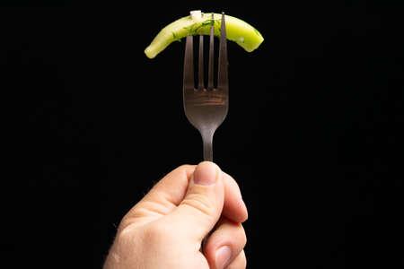 Slice of fresh green cucumber on fork in the hand on dark black background. Zdjęcie Seryjne