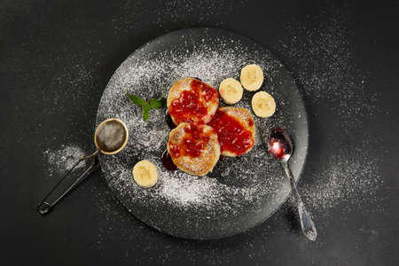 Cottage cheese pancakes on a black plate sprinkled with powdered sugar. Homemade food. Syrniki with fresh mint. Фото со стока