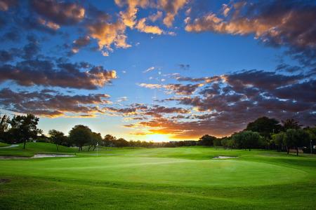 Zonsondergang over de golfbaan Stockfoto