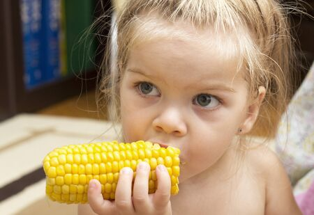 babygirl: Little cute blonde babygirl eating boiled corn Stock Photo