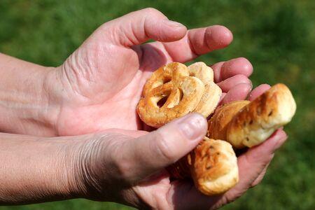 women's hand: Womens hand holding salted pretzels Stock Photo