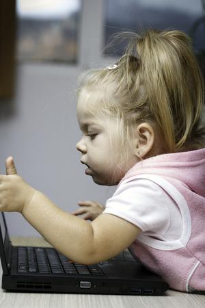 data sheet: Little girl using laptop for bussines figures, data sheet Stock Photo