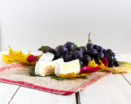 winy: Autumn background with well colored leafs, grapes and cheese on a rustic fabric texture Stock Photo
