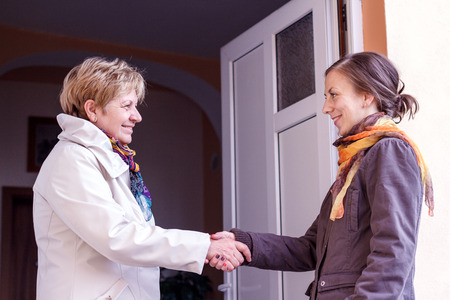 greet: Senior women greeting young girl in the doorway Stock Photo