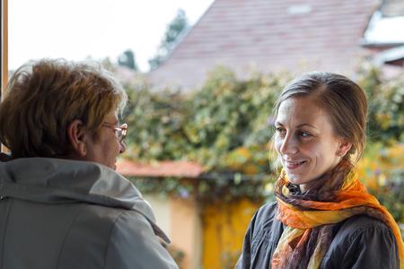 Senior women greeting young girl in the doorway