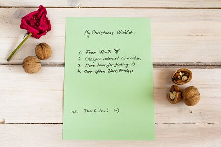 christmas list: Funny christmas list for Santa on a white natural wooden background, green paper Stock Photo