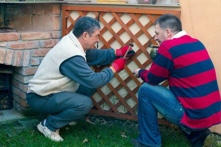 younger man: Younger man helping senior man is gardening, household activity