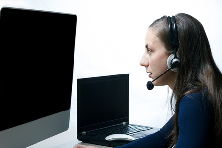public safety: Young girl wearing headset in fornt of two monitors at a Public Safety Answering Point