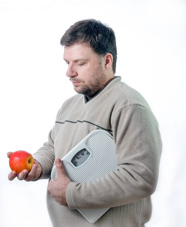 loosing: Adult men holding bathroom scale looking at a healthy apple. Staying healthy and loosing weight