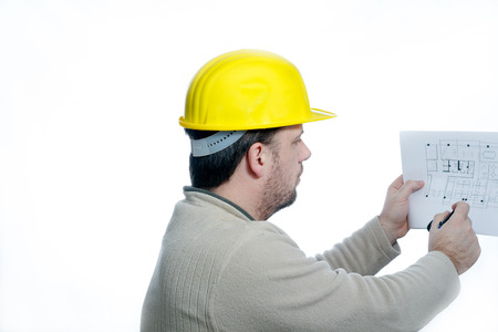 yelow: Young construction engineer wearing a yelow helmet reads a construction plan printed on paper