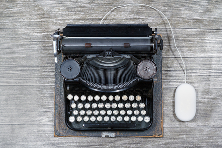 mechanical mouse: Old typewriter on white  background along a modern technology mouse