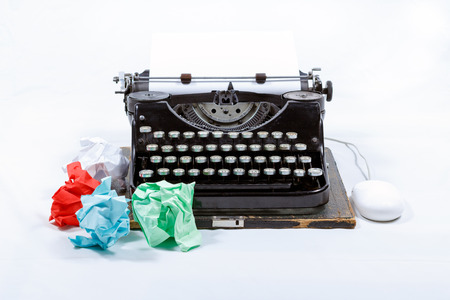 mechanical mouse: Old typewriter on a textured grey background along with a bunch of colored papers and a wired mouse