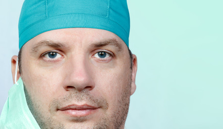 eyes looking down: Adult male doctor portrait close up on green blue background